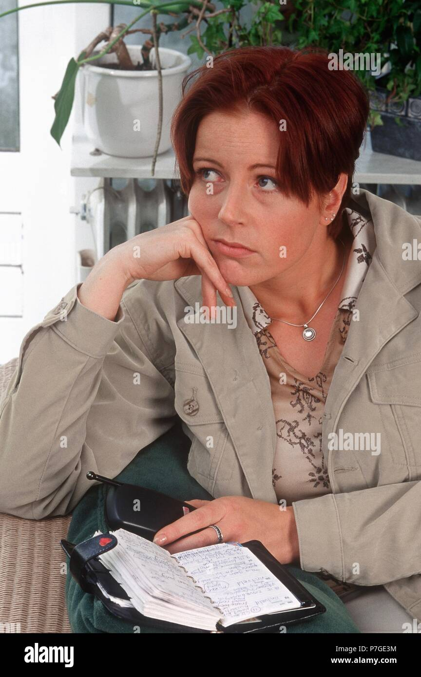 100-013-053 Woman contemplating with agenda on sofa - Stock Image
