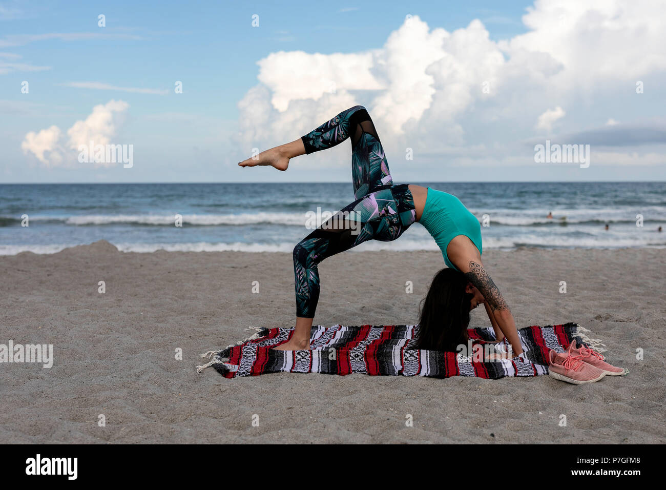 A Young woman doing a yoga workout on the beach by herself wearing yoga pants - Stock Image