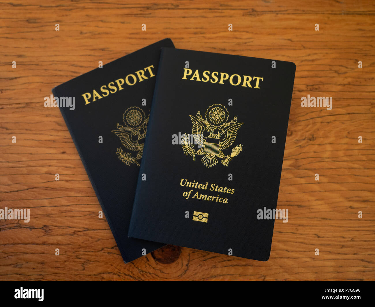 Two navy blue US Passports on a wooden table top and photographed from above. - Stock Image