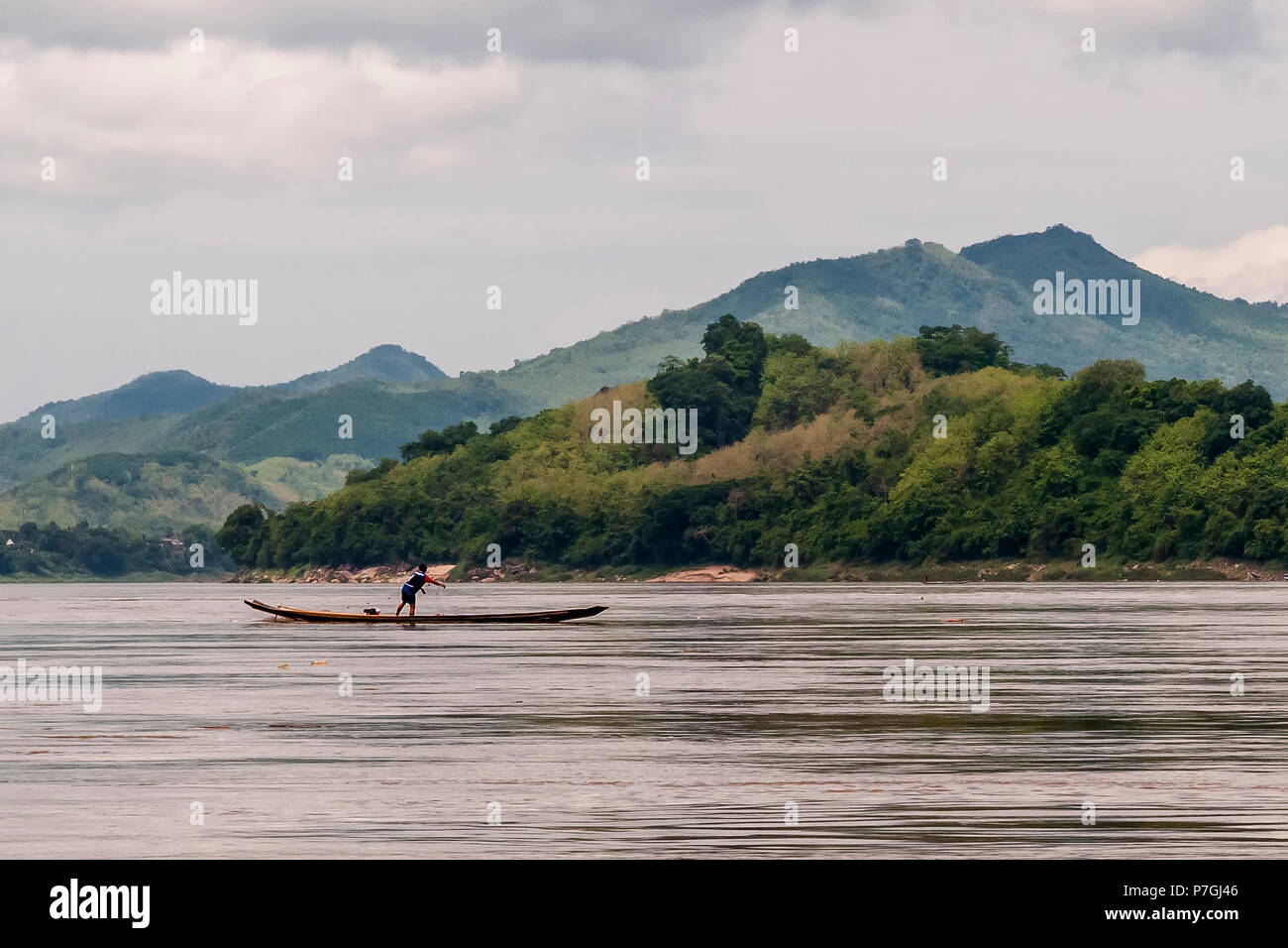 Fisherman poised on the boat launches the net on the Mekong River, Luang Prabang, Laos - Stock Image