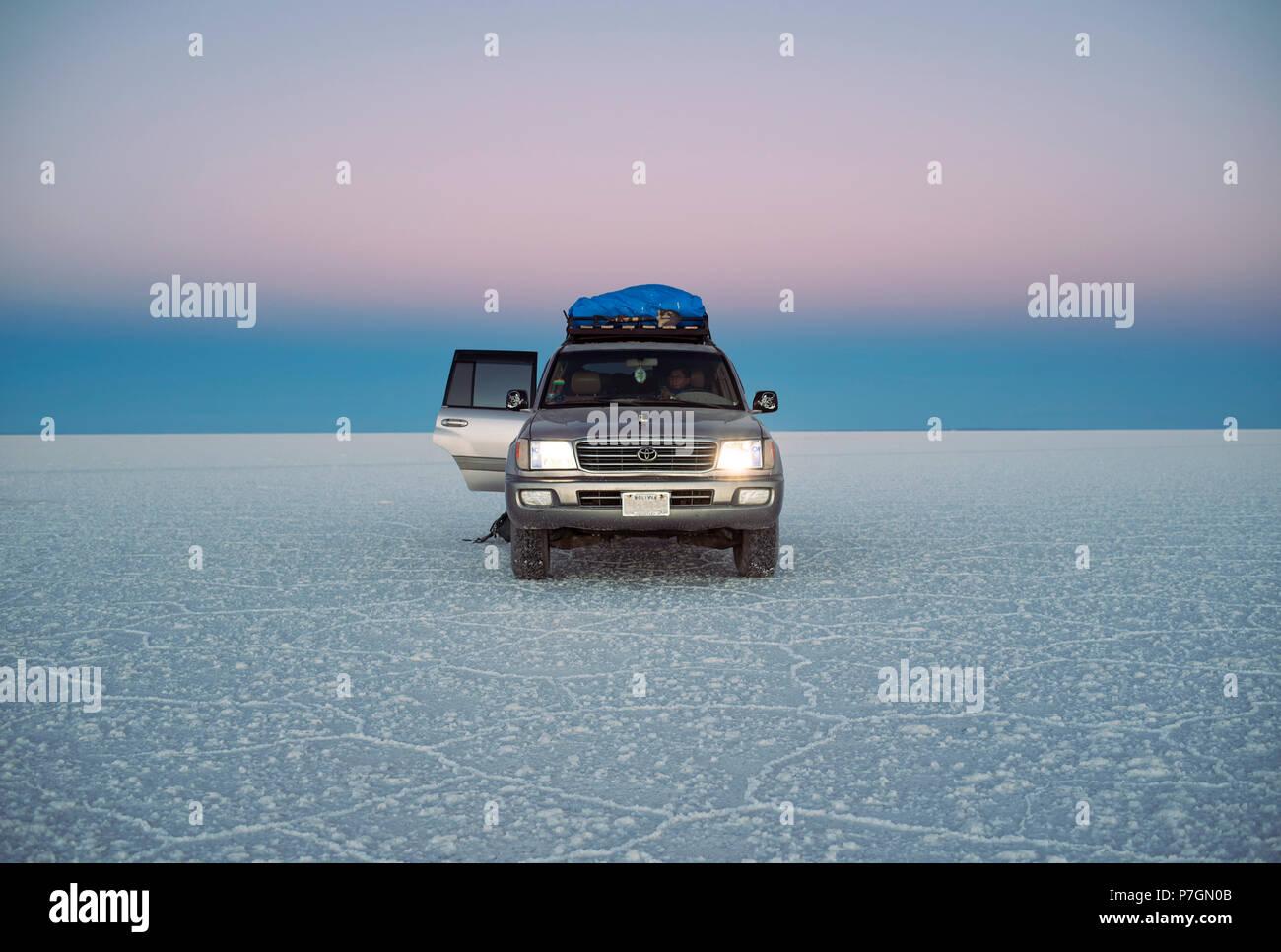 Land Cruiser during twilight in Uyuni salt flats (Salar de Uyuni) Bolivia, South America. Jun 2018 - Stock Image