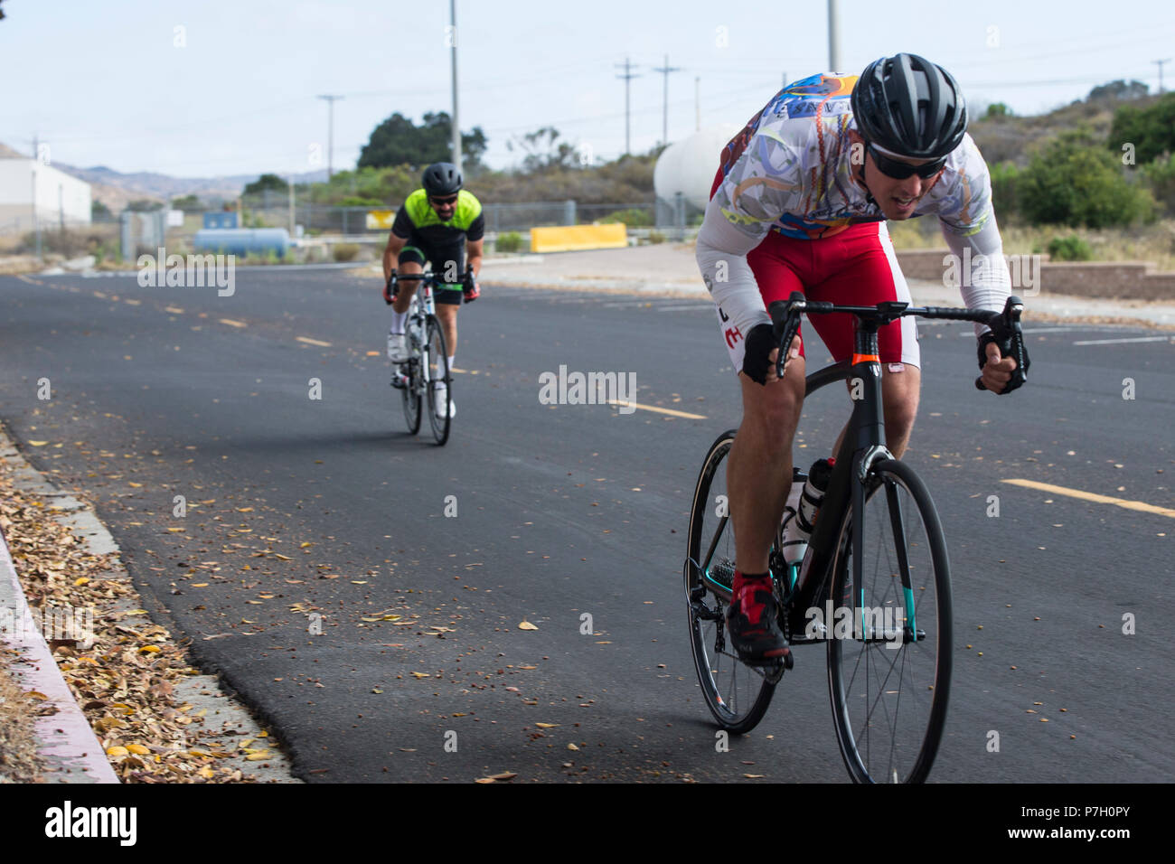 U.S. Marine Corps Staff Sgt. James Dunaway, right, infantry unit leader, Wounded Warrior Battalion-West, and retired Master Sgt. Mark Mann, left, volunteer, perform timed trials at Marine Corps Base Camp Pendleton, California, June 26, 2018. Dunaway and his coaches haved trained several months cycling over 30 miles a day, five days a week. (U.S. Marine Corps photo by Lance Cpl. Drake Nickels) - Stock Image