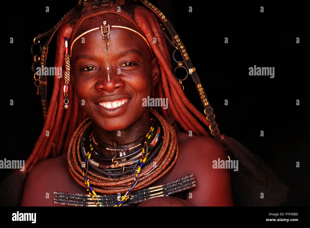 Portrait of a married Himba woman, smiling, Kunene District, Kaokoveld, Namibia - Stock Image