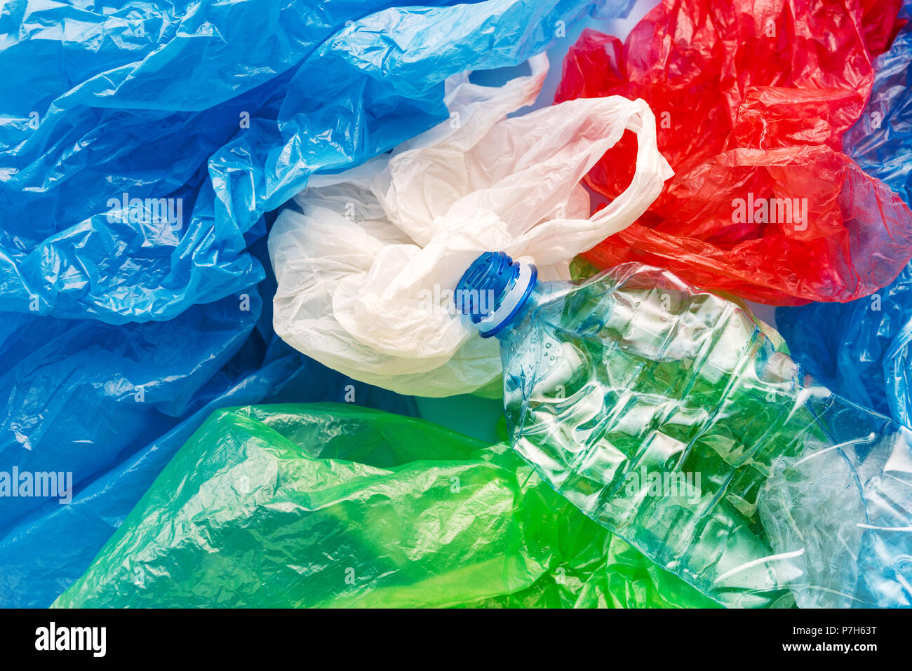 Pile of colorful plastic bags and bottle, consumerism and environmental pollution concept - Stock Image