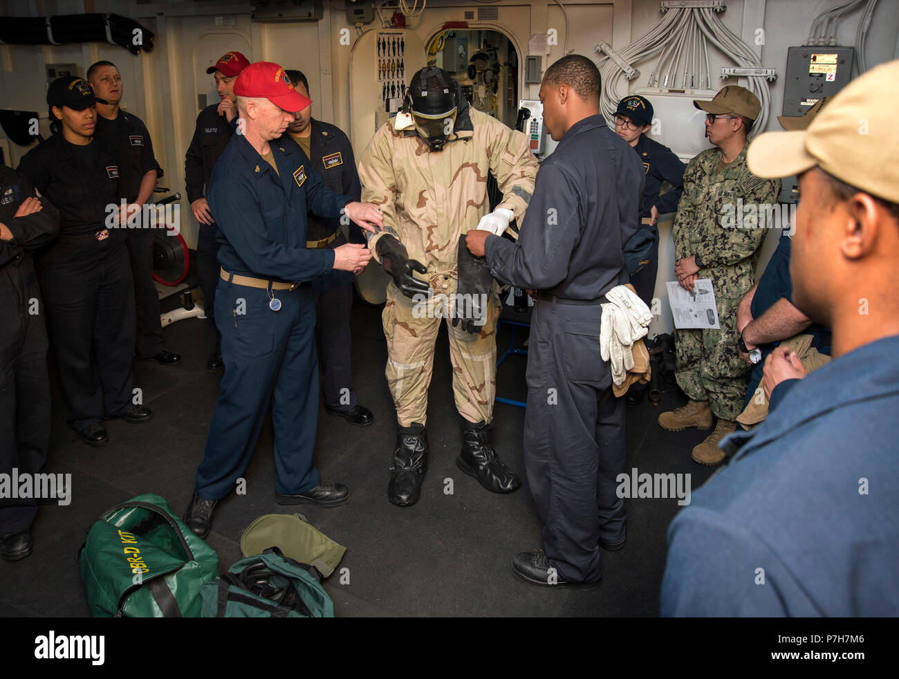 180626-N-WF272-095 SAN DIEGO (June 26, 2018) Senior Chief Culinary Specialist Anthony Hooper, left, and Ship's Serviceman Seaman Jaylan Eady, right, from Whiteville, N.C., help Logistics Specialist 2nd Class Donald Eugene, from Miami, don a chemical, biological and radiological (CBR) overgarment during a CBR training exercise aboard the amphibious assault ship USS Bonhomme Richard (LHD 6). Bonhomme Richard is currently in its homeport of San Diego, preparing for an upcoming scheduled deployment. (U.S. Navy photo by Mass Communication Specialist 1st Class Diana Quinlan/Released) - Stock Image