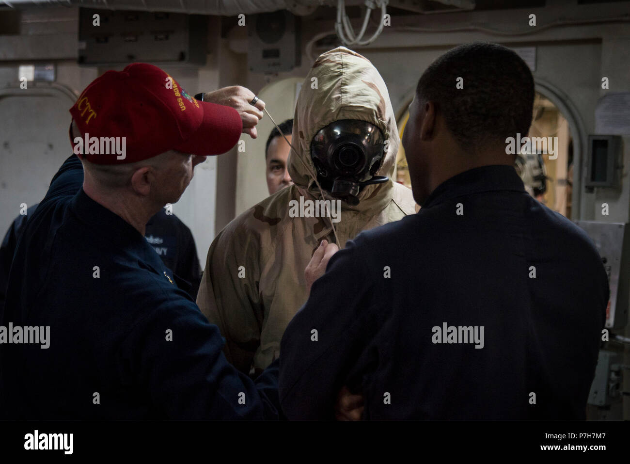 180626-N-WF272-100 SAN DIEGO (June 26, 2018) Senior Chief Culinary Specialist Anthony Hooper, left, and Ship's Serviceman Seaman Jaylan Eady, right, from Whiteville, N.C., help Logistics Specialist 2nd Class Donald Eugene, from Miami, don a chemical, biological and radiological (CBR) overgarment during a CBR training exercise aboard the amphibious assault ship USS Bonhomme Richard (LHD 6). Bonhomme Richard is currently in its homeport of San Diego, preparing for an upcoming scheduled deployment. (U.S. Navy photo by Mass Communication Specialist 1st Class Diana Quinlan/Released) - Stock Image