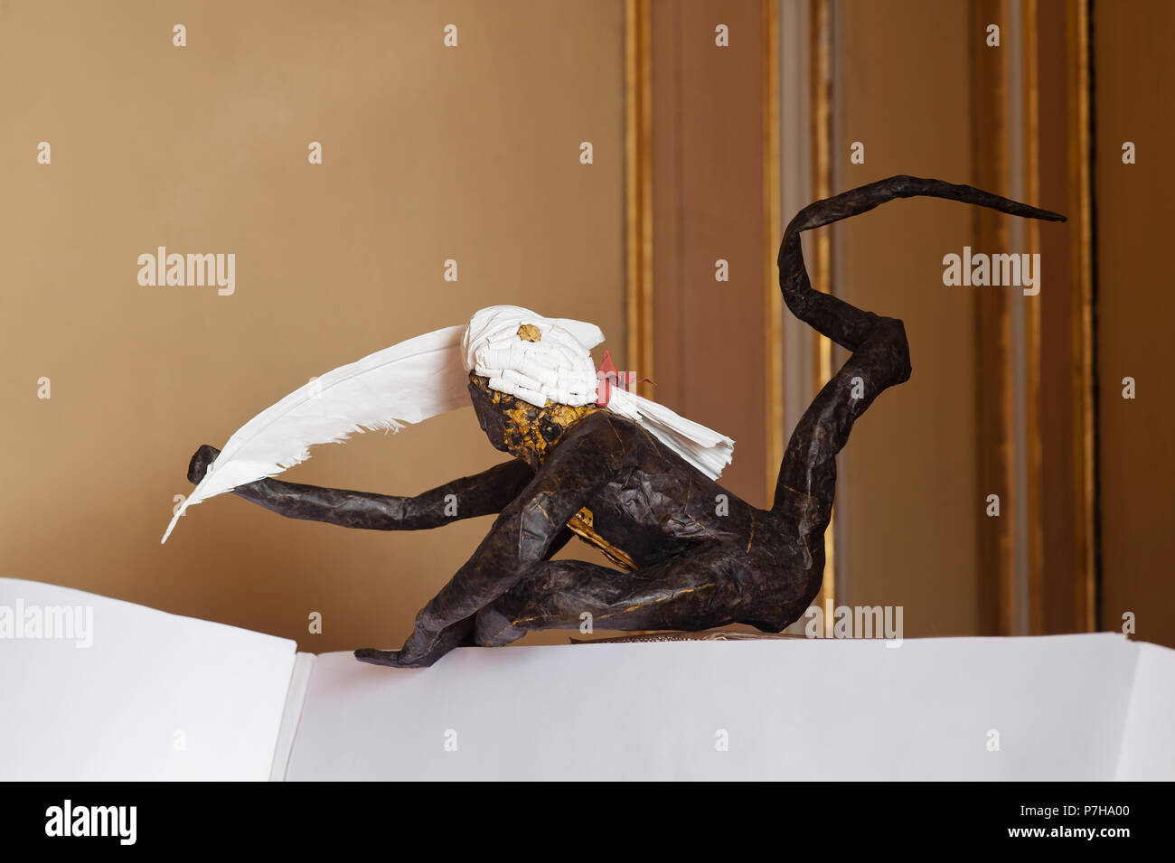 Paper sculpture of monkey holding quill - Stock Image