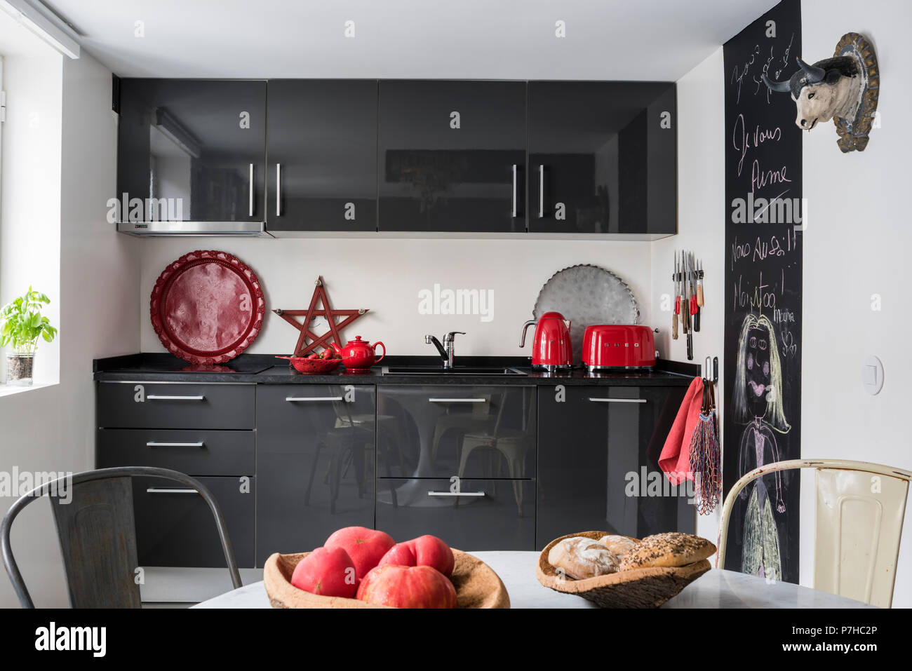 Dark Grey Flat Fronted Kitchen Units In Modern Kitchen With Vintage Tolix Metal Dining Chairs Stock Photo Alamy