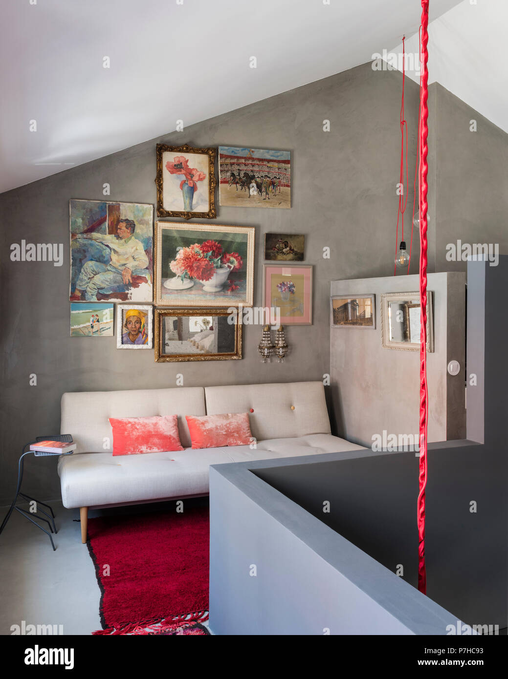 Colourful mix of still lifes and portraits on wall of seating area in modern loft style apartment - Stock Image
