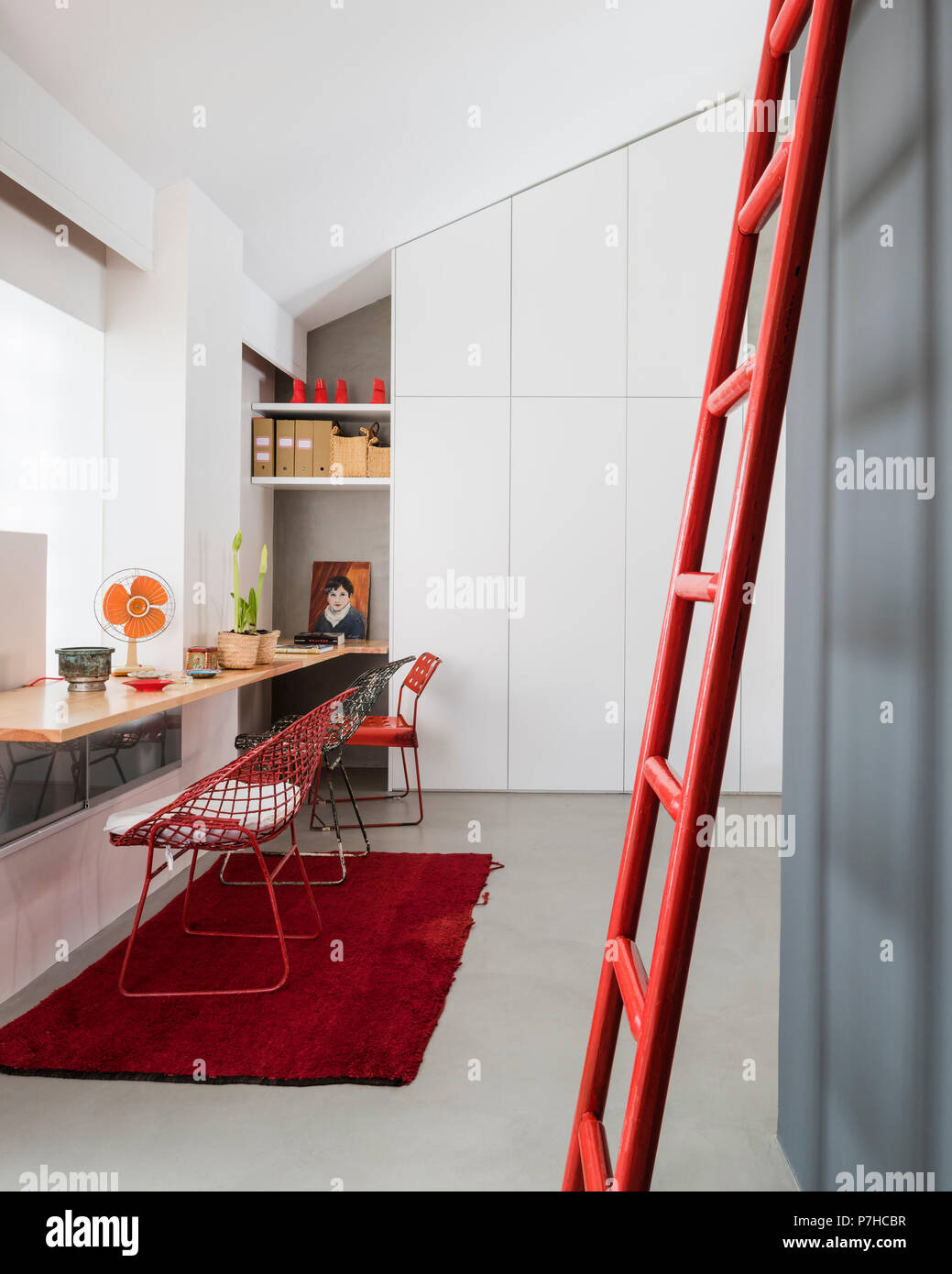 Wire basket chairs at timber work surface in loft style apartment. A red ladder leans in the foreground - Stock Image