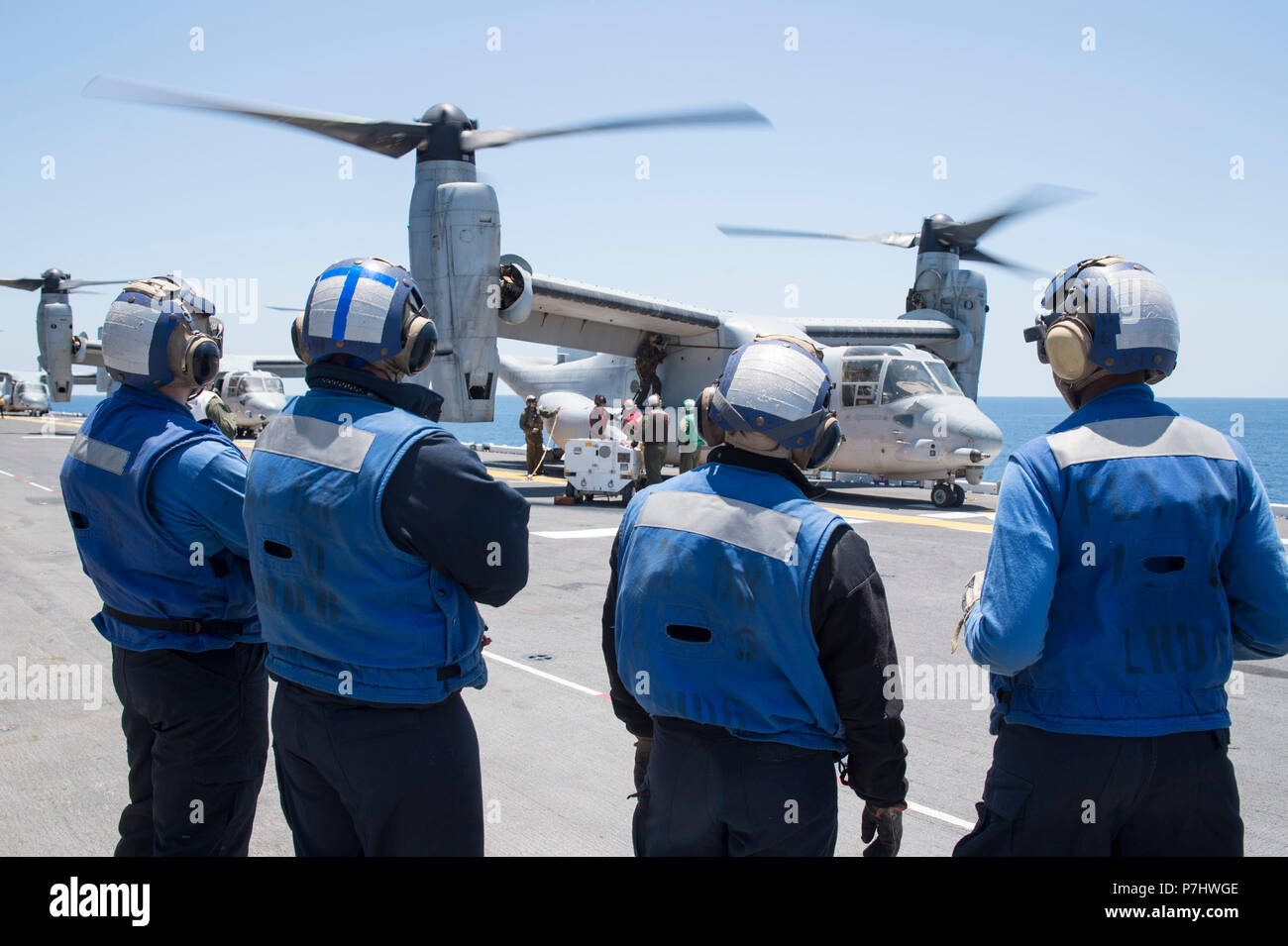 """180703-N-RD713-218 PACIFIC OCEAN,  (July 3, 2018) Air department Sailors, assigned to the amphibious assault ship USS Bonhomme Richard (LHD 6), look on as MV-22B Ospreys, assigned to the """"Red Lions"""" of Marine Medium Tiltrotor Squadron (VMM) 363, embark the ship. Bonhomme Richard is currently underway in the U.S. 3rd Fleet area of operations. (U.S. Navy photo by Mass Communication Specialist 3rd Class Zachary DiPadova) Stock Photo"""