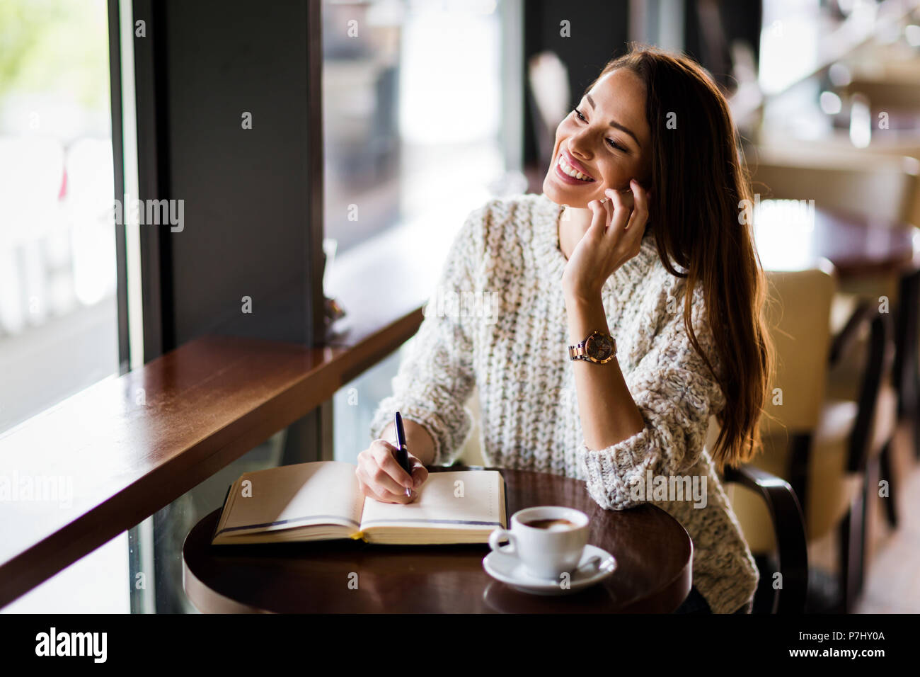 Portrait of happy young woman in cafe - Stock Image