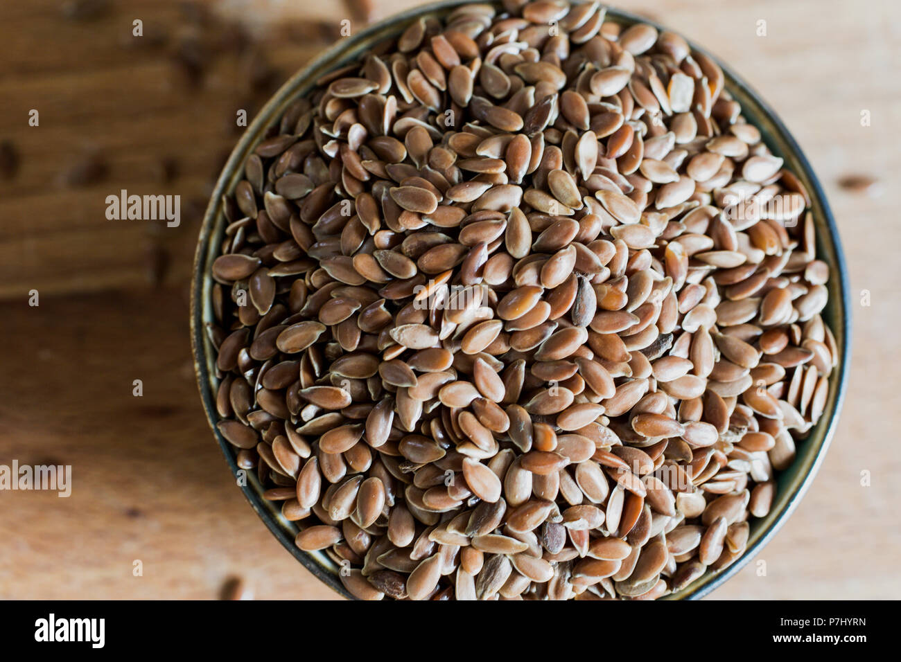 healthy raw diet linseed flaxseed grain cereal in bowl on wooden table - Stock Image