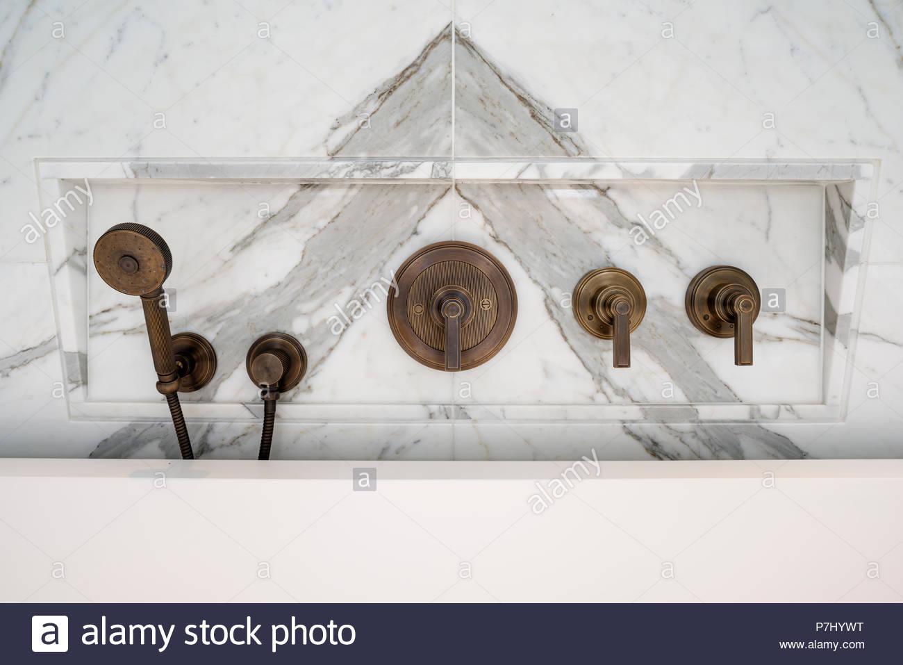 Metal taps by bathtub - Stock Image