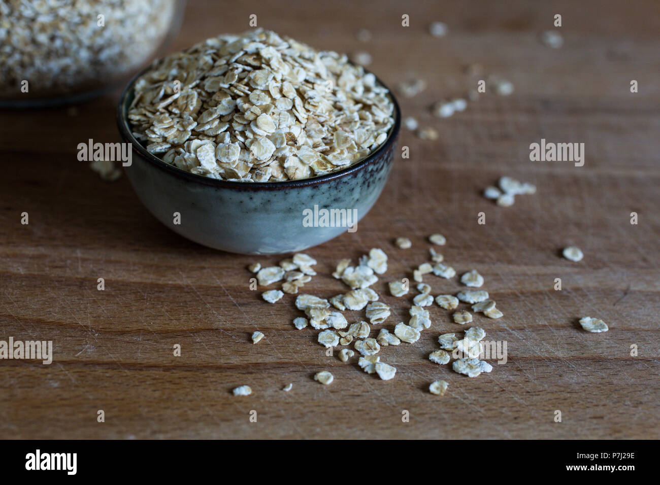 rolled oats for porridge in heap in ceramic bowl on wooden table - Stock Image