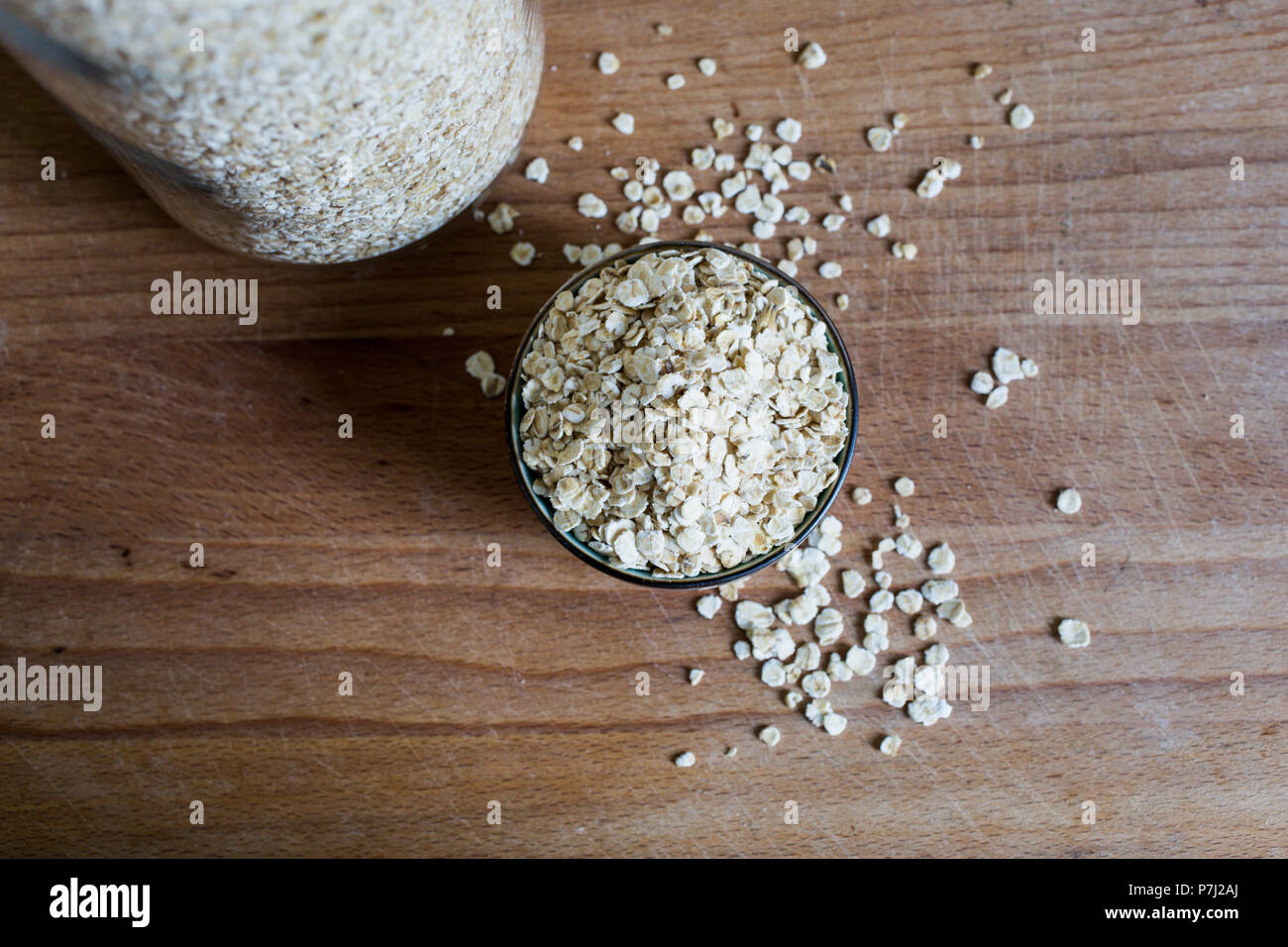 fibre source natural oat flakes for whole food diet on wooden table - Stock Image