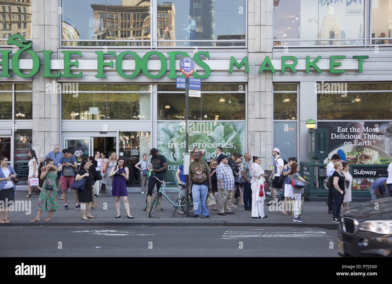 People wait for the cross town bus on 14th Street in front of the Whole Foods Market across the street from Union Square. New York City. - Stock Image