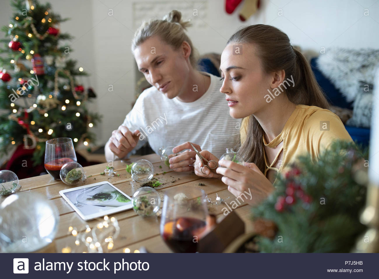 young couple with digital tablet learning how to make miniature terrarium christmas ornaments