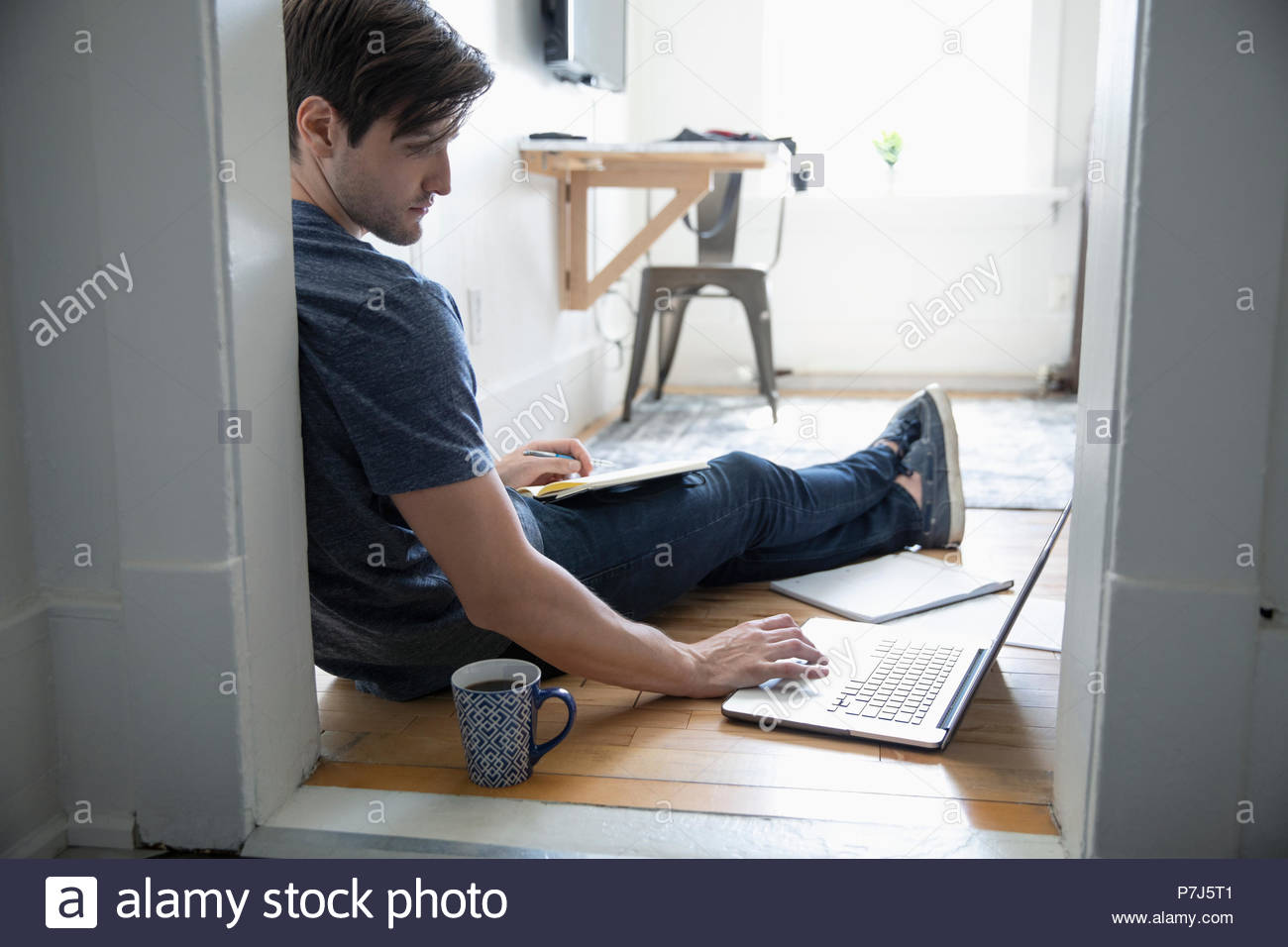 Young man drinking coffee and using laptop on floor - Stock Image