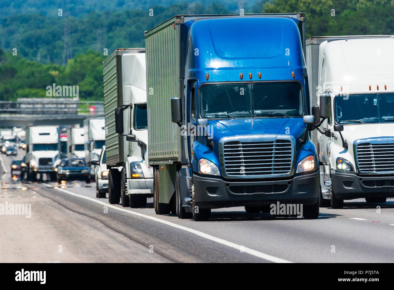 A long steady line of truck traffic on a busy interstate. Image shot on hot day. Heat waves from asphalt create distortion, especially on vehicles far - Stock Image