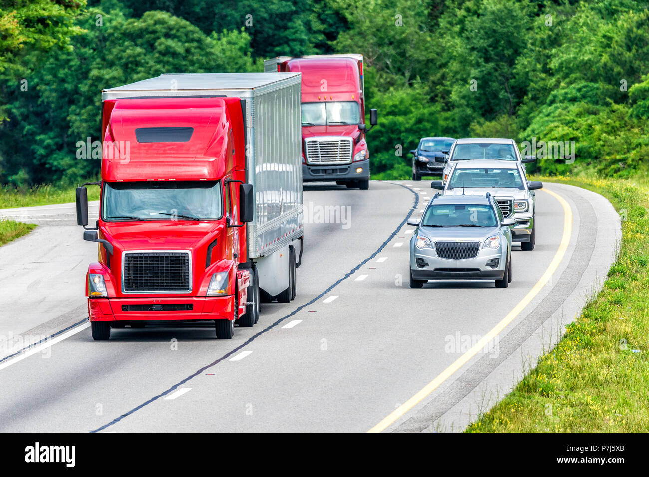 Two 18-wheelers and several passenger vehicles travel down an interstate.  Note: All logos and identifying marks have been removed from all vehicles.  - Stock Image