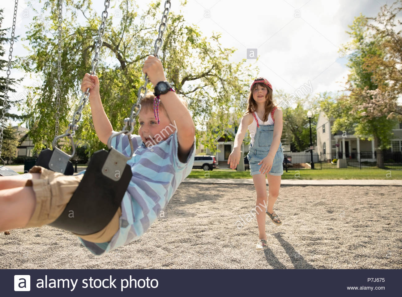 Sister pushing brother on swing at sunny playground - Stock Image