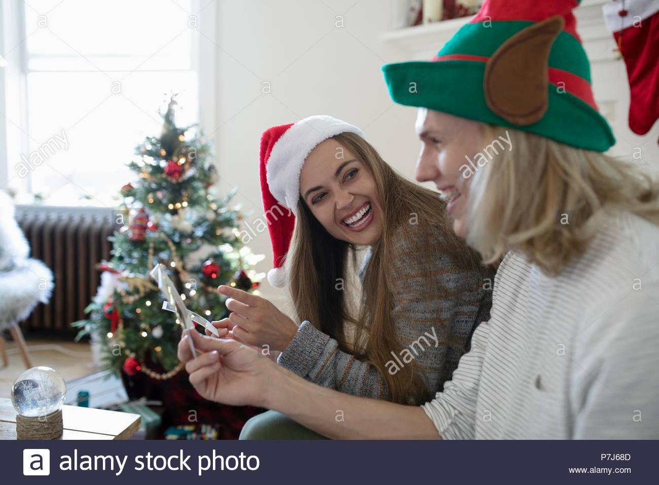 25e4e7c6913e2 Playful young couple wearing Christmas Santa and elf hats - Stock Image