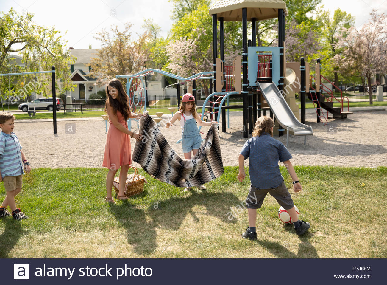 Mother and kids playing, spreading picnic blanket in sunny park - Stock Image