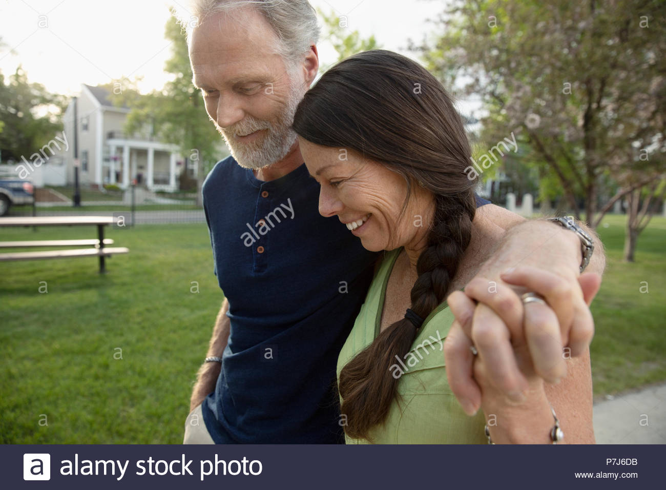 Affectionate senior couple holding hands and walking in park - Stock Image