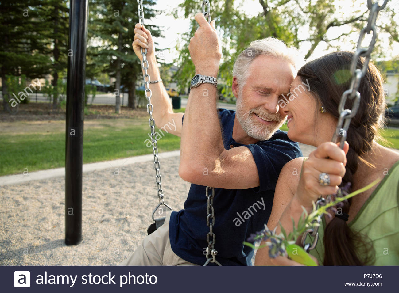Affectionate senior couple on swings at playground - Stock Image