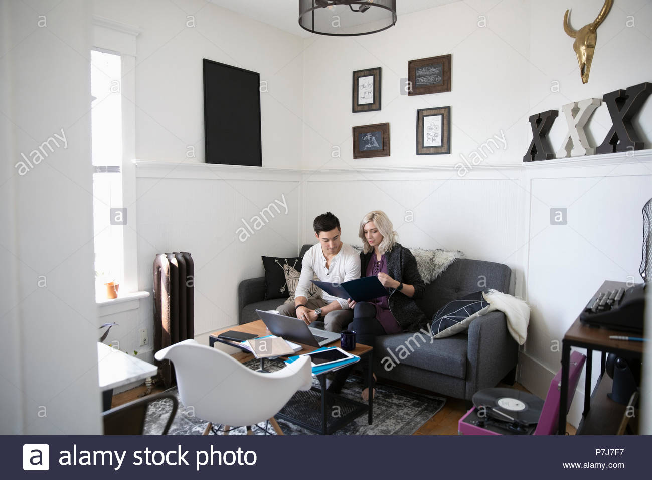 Young couple looking at finances in living room - Stock Image