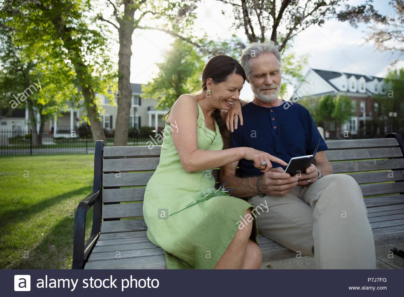 Senior couple using digital tablet on park bench - Stock Image