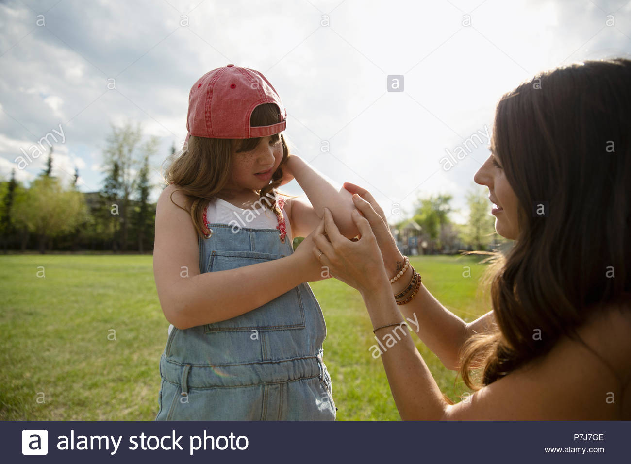 Mother checking injury on daughters elbow in park - Stock Image