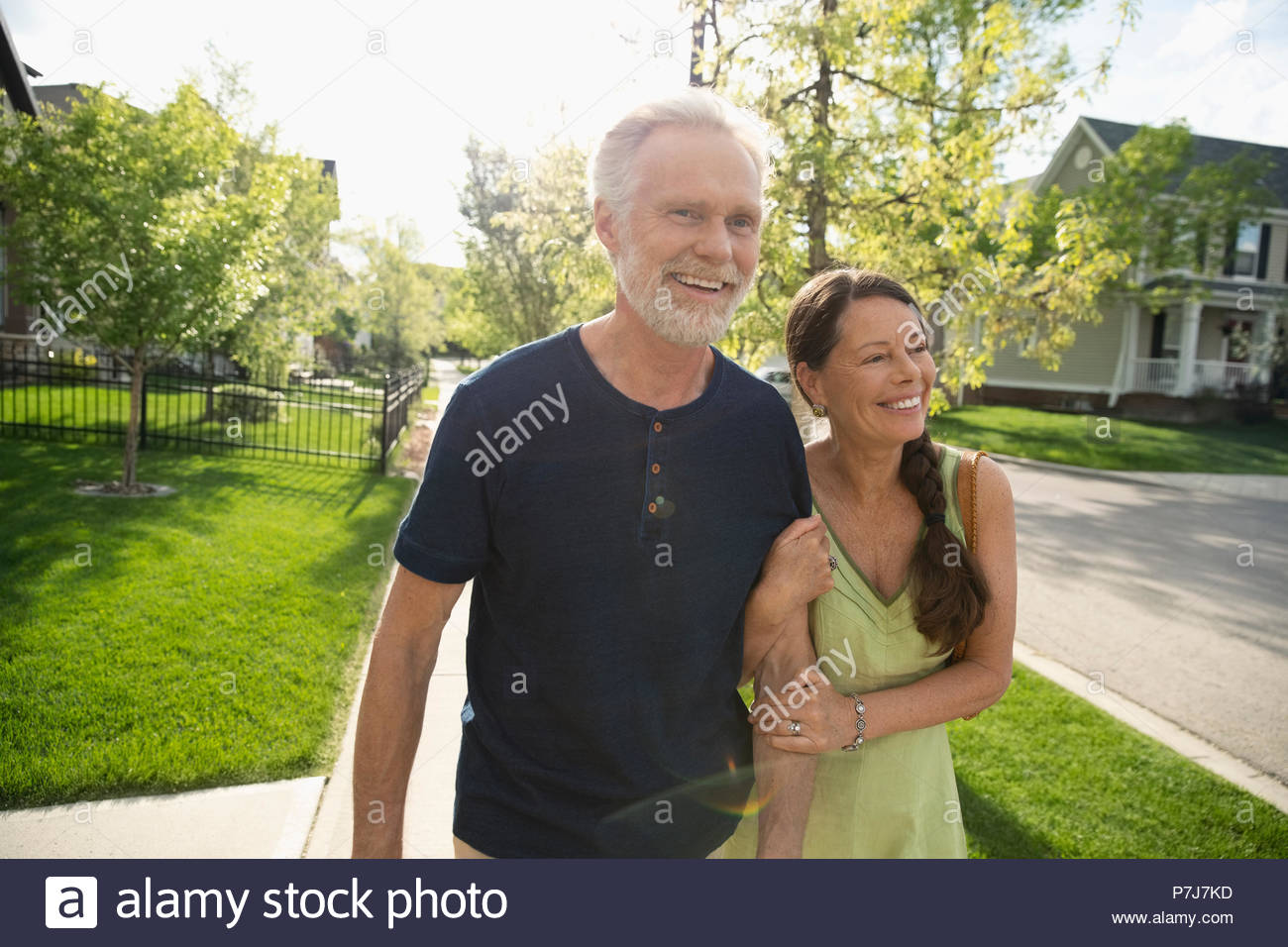 Smiling, affectionate senior couple walking arm in arm on sunny neighborhood sidewalk - Stock Image