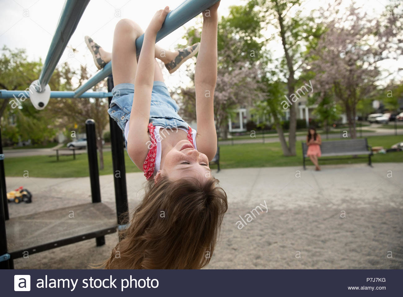 Playful girl hanging upside down from monkey bars at playground - Stock Image