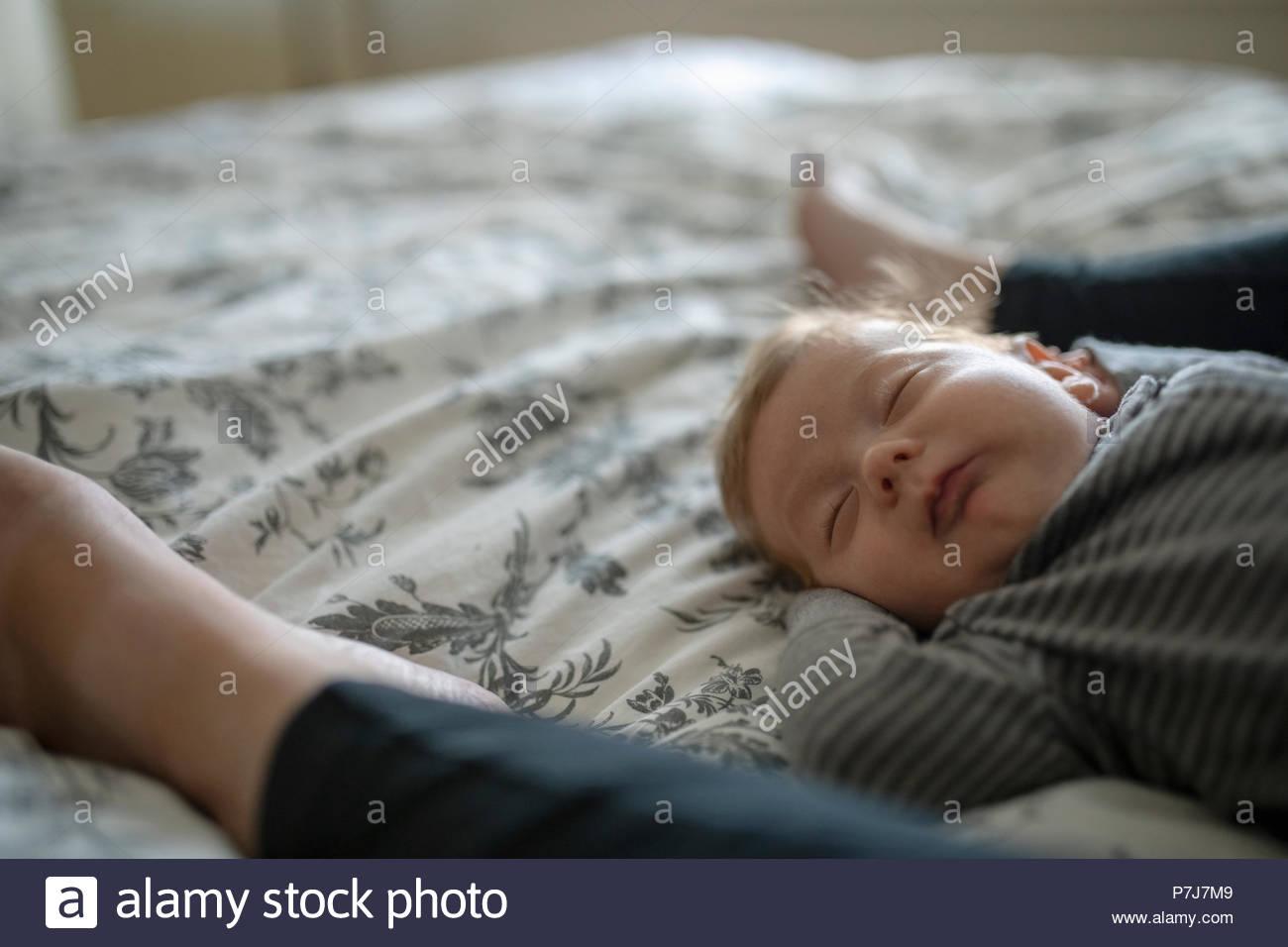 Serene baby boy sleeping between mothers legs on bed - Stock Image