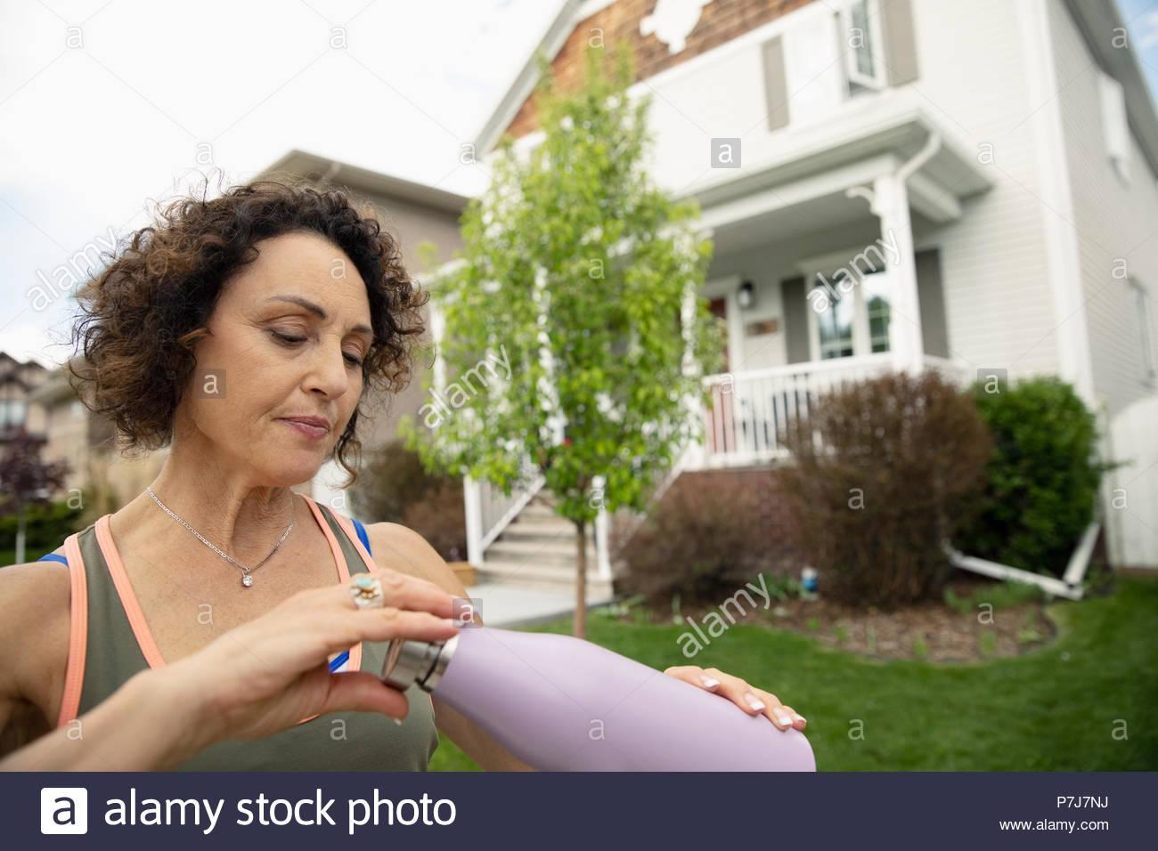 Senior female runner drinking from water bottle on neighborhood sidewalk - Stock Image
