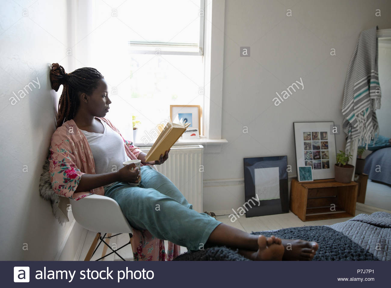 Young woman relaxing, drinking coffee and reading book in bedroom Stock Photo