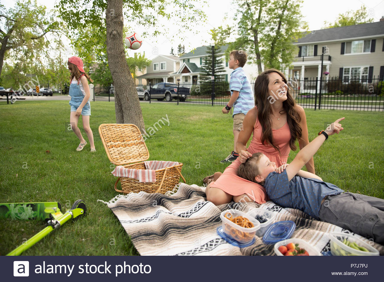 Affectionate mother and son relaxing, enjoying picnic in park - Stock Image