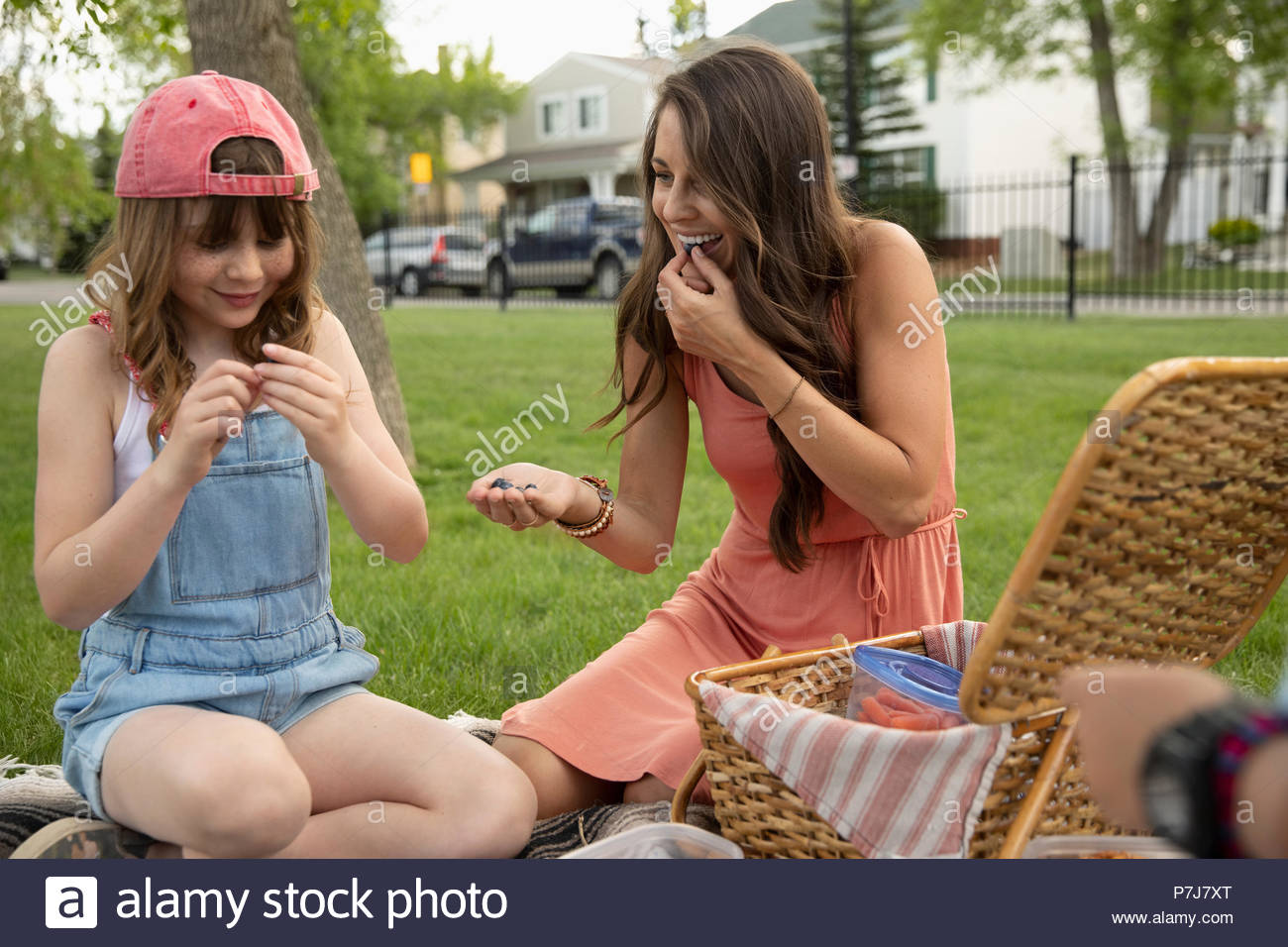 Mother and daughter eating, enjoying picnic in park - Stock Image