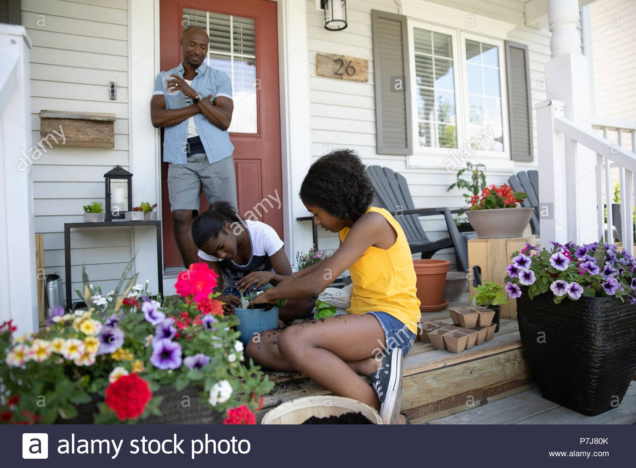 Father watching tween daughters potting flowers on front stoop - Stock Image