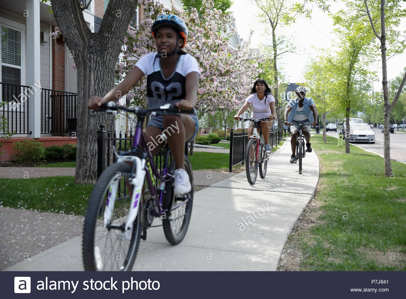 Family bike riding on neighborhood sidewalk - Stock Image