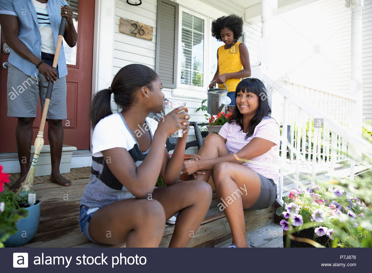 Family bonding, sweeping and watering flowers on front stoop - Stock Image