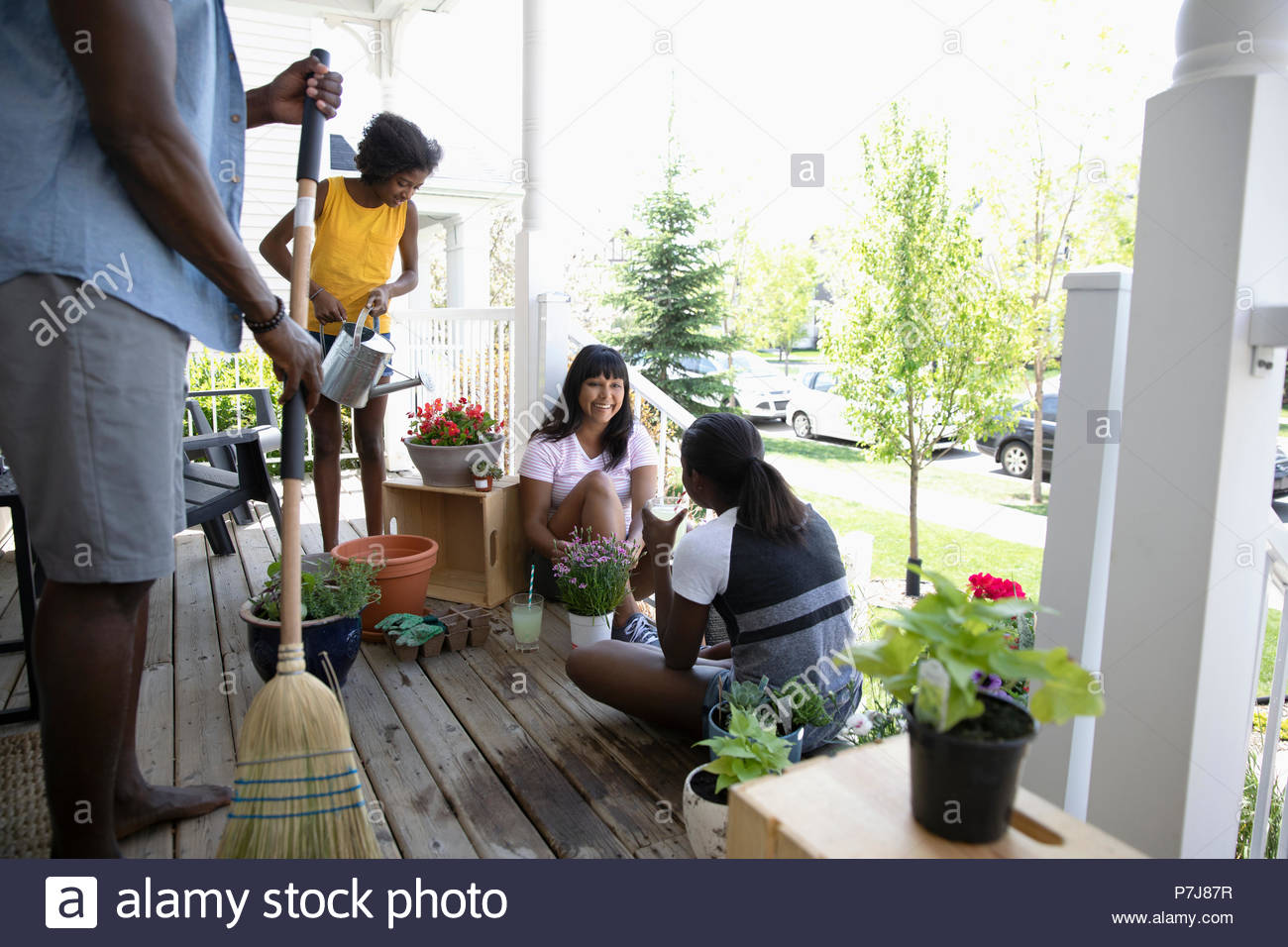 Family gardening, planting flowers and sweeping on front stoop - Stock Image
