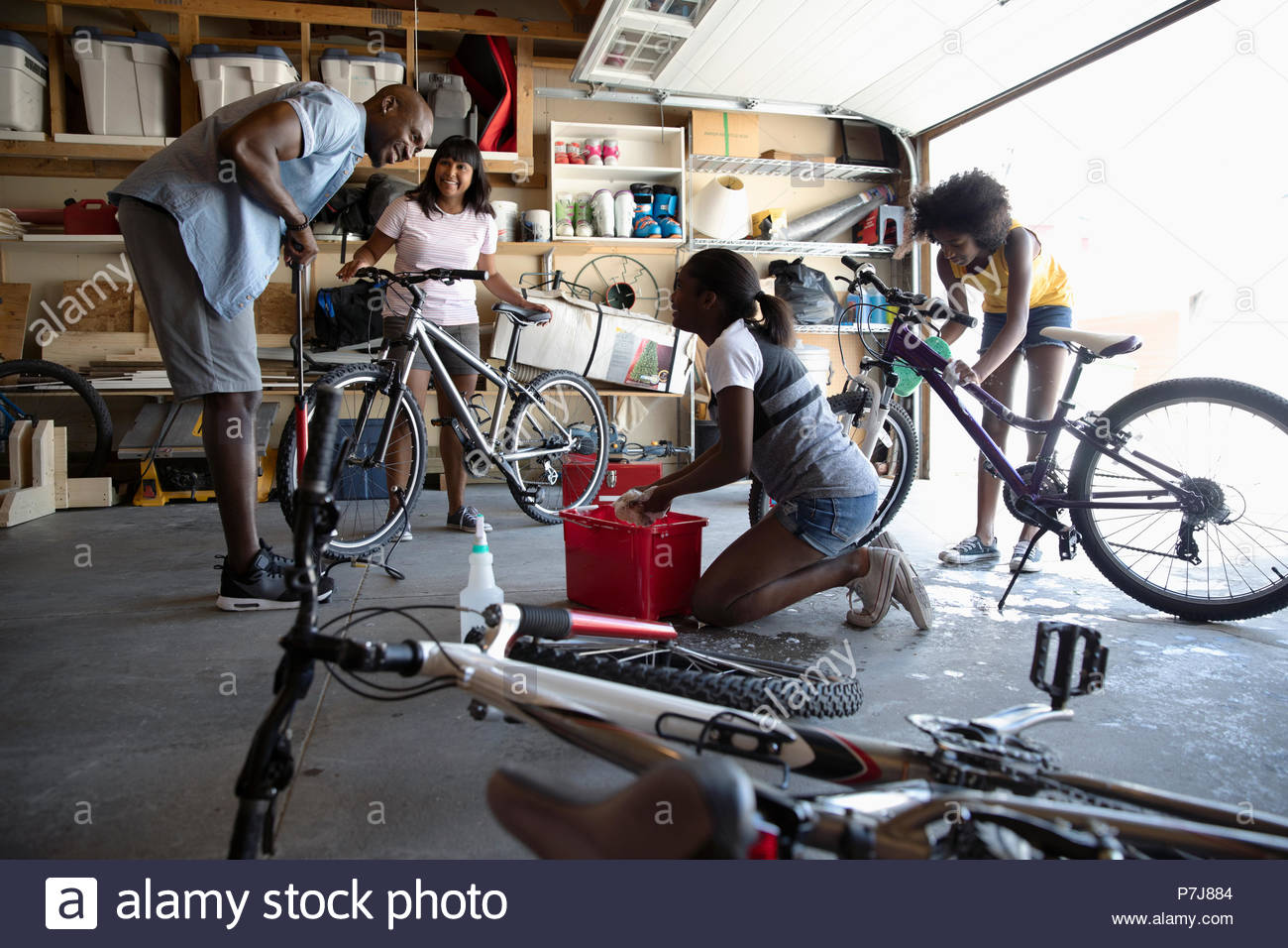 Family fixing bicycles in garage - Stock Image