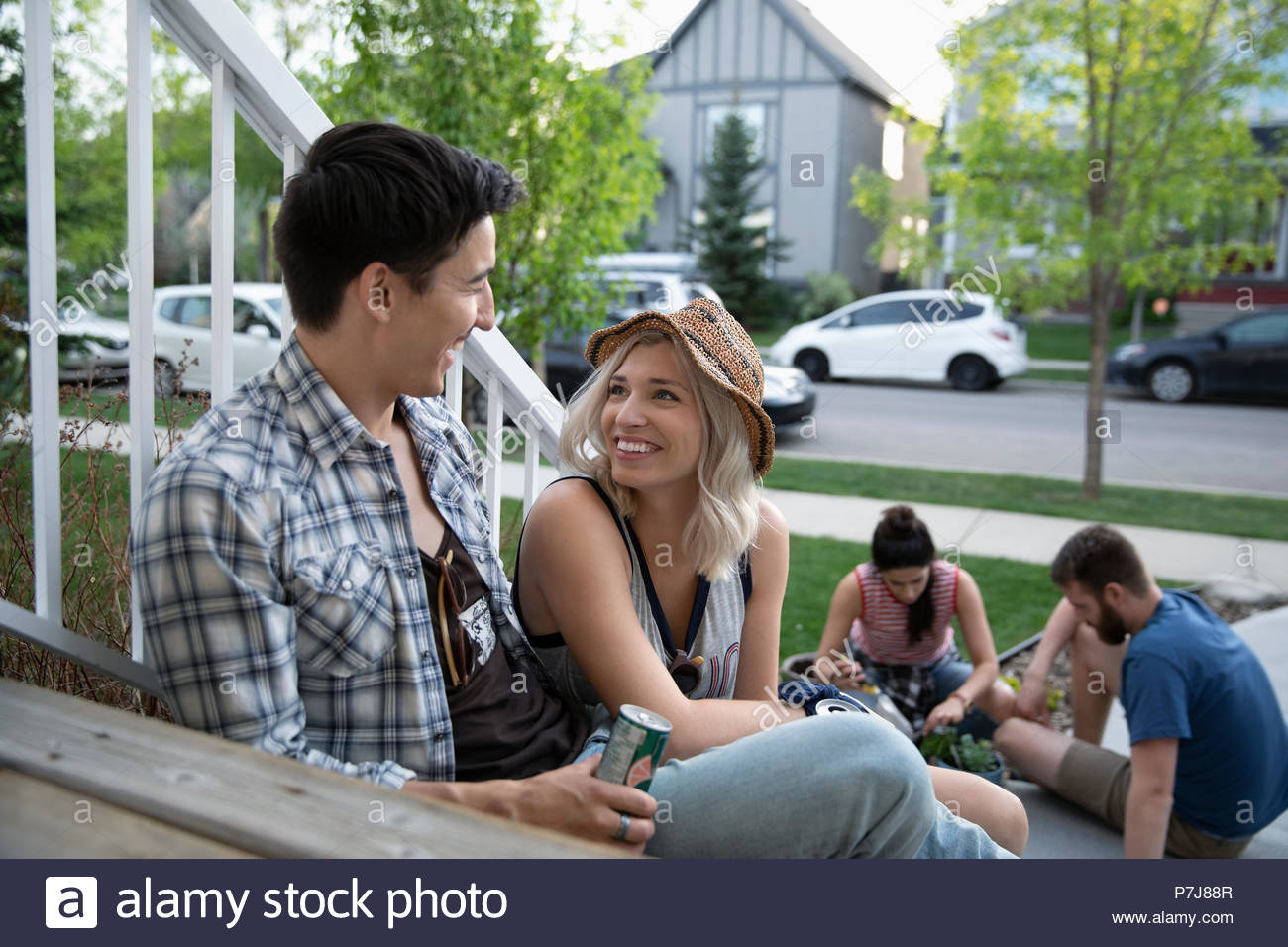 Smiling couple taking a break from gardening with friends on front stoop - Stock Image