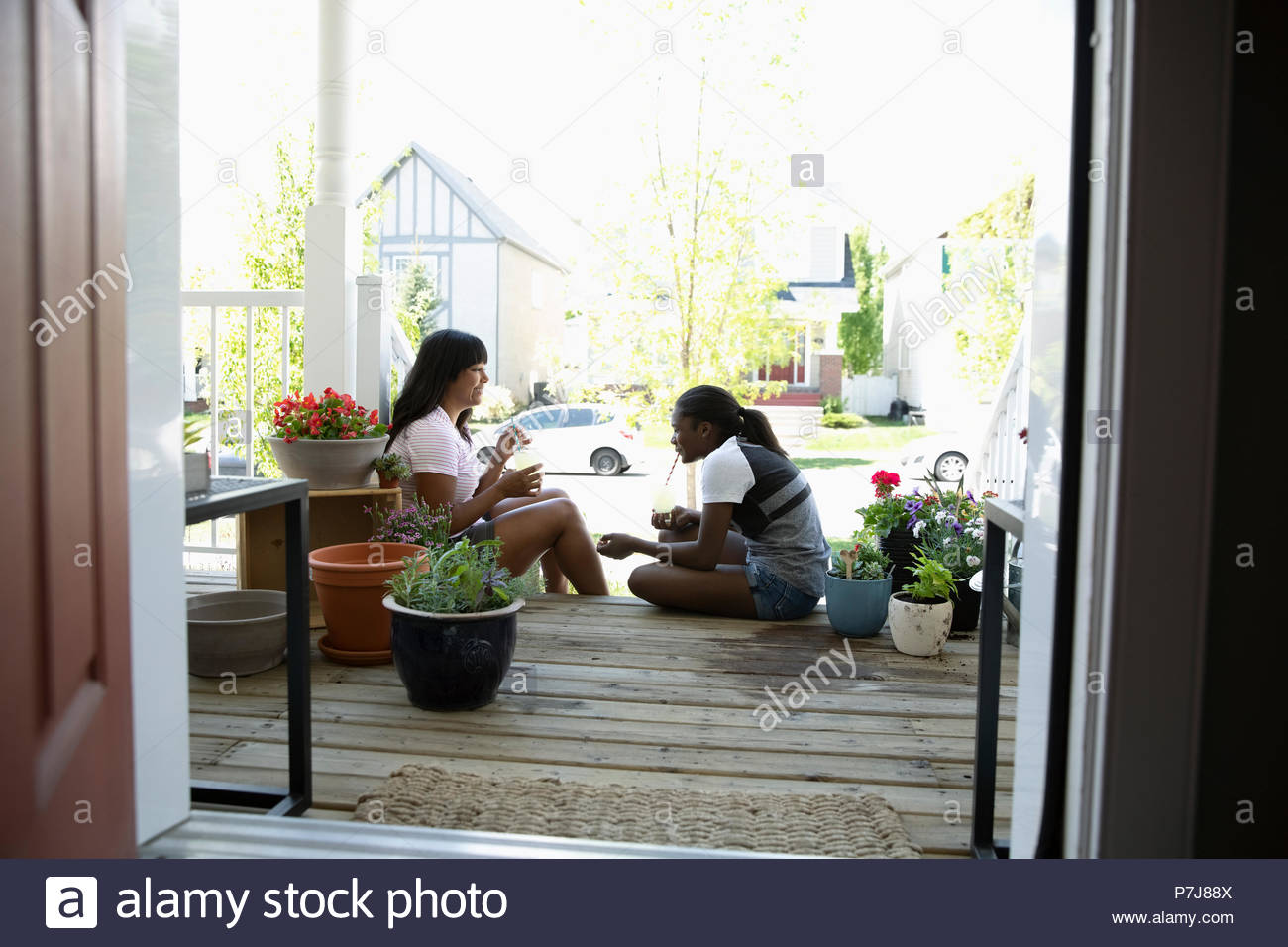 Mother and daughter bonding, talking and planting flowers on front stoop - Stock Image