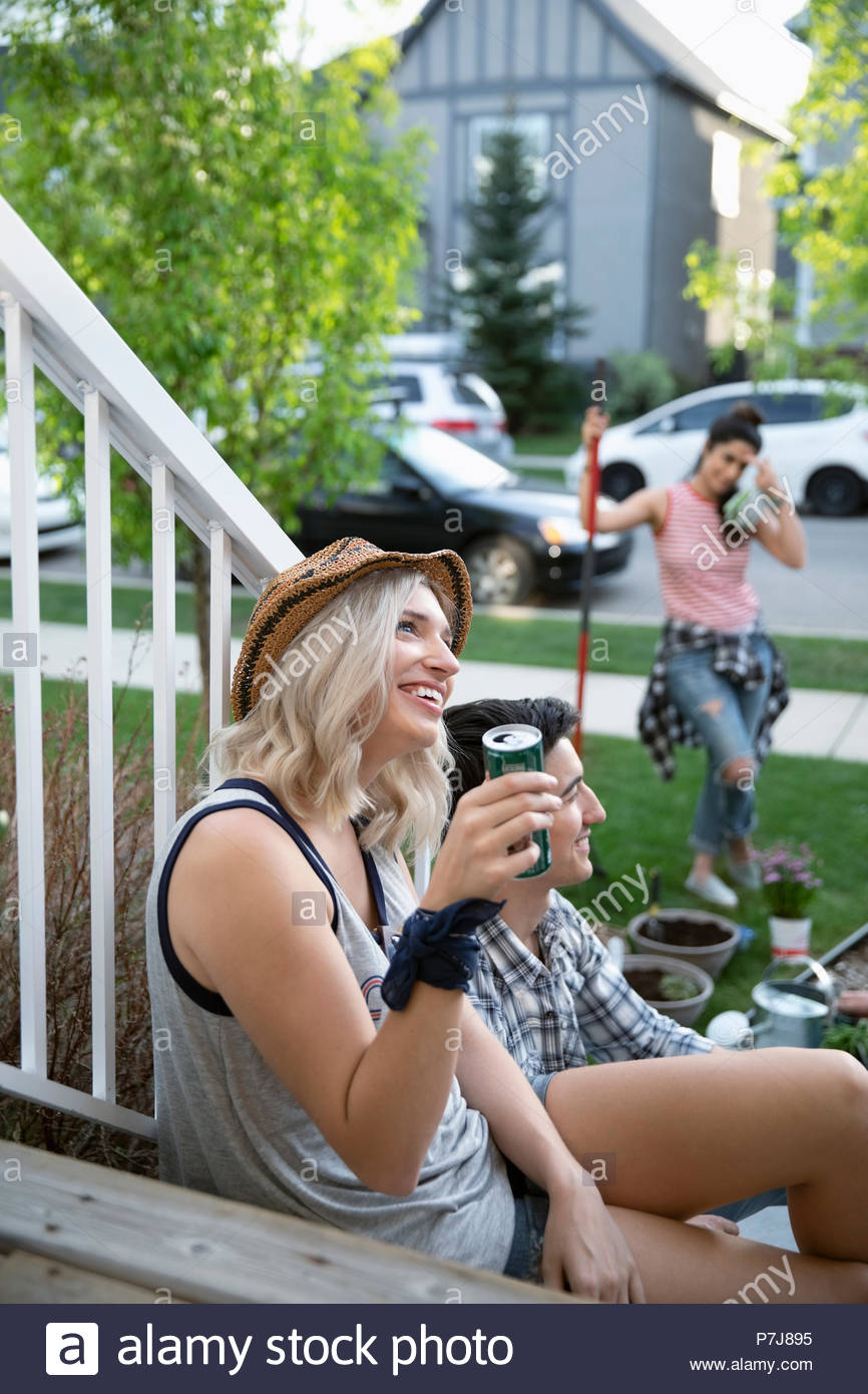 Smiling woman taking a break from gardening with friends on front stoop - Stock Image