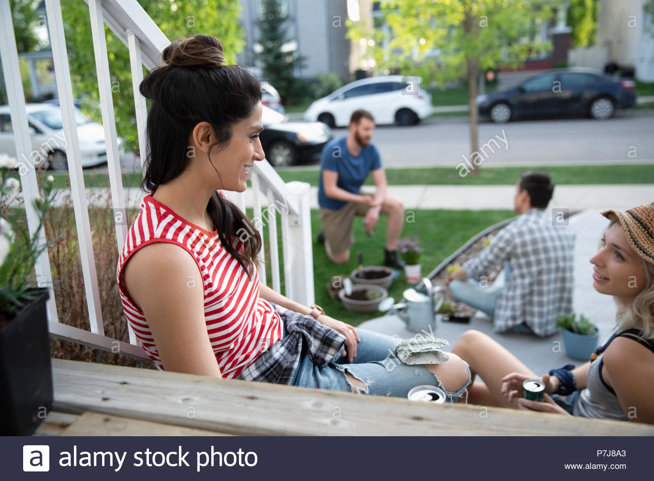 Neighbors gardening, taking a break and talking on front stoop - Stock Image