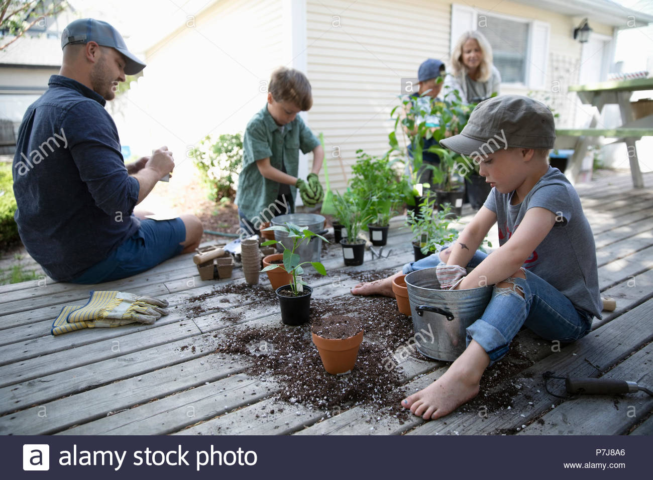 Family potting plants on deck - Stock Image